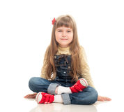 Cute little girl wearing jeans overall sitting on the floor and Royalty Free Stock Photo