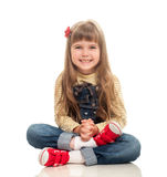 Cute little girl wearing jeans overall sitting on the floor and. Smiling on white background Royalty Free Stock Photos