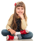 Cute little girl wearing jeans overall sitting on the floor and. Smiling on white background Royalty Free Stock Photo
