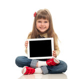 Cute little girl wearing jeans overall sitting on the floor with. Tablet computer and smiling on white background Royalty Free Stock Images