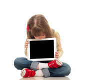 Cute little girl wearing jeans overall sitting on the floor with Stock Image