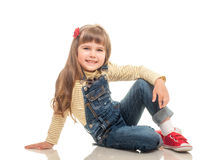 Cute little girl wearing jeans overall sitting on the floor and Royalty Free Stock Photography