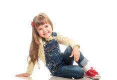 Cute little girl wearing jeans overall sitting on the floor and Royalty Free Stock Image