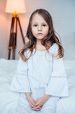 Cute little girl wearing nightgown sitting on the bed. Cute little girl wearing nightgown sitting on the bed in bedroom, childhood concept, indoor vertical Royalty Free Stock Photos