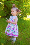 Cute little girl wearing polka dots dress in a park Stock Image