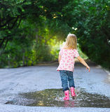 Cute little girl wearing rain boots Stock Images