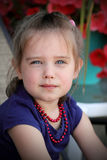 Cute little girl wearing red beads. A cute precious little 4 year old girl with blue eyes, purple shirt and red beads, Shallow depth of field Royalty Free Stock Image