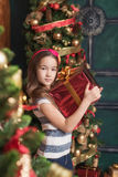 Cute little girl wearing red headband holding gift near christmas tree. Cute little girl wearing red headband holding gift near christmas tree Stock Photo