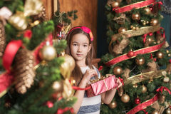 Cute little girl wearing red headband opens gift near christmas tree. Stock Photos