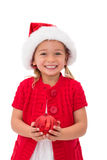 Cute little girl wearing santa hat holding bauble Stock Photography