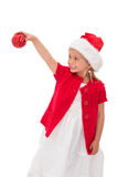 Cute little girl wearing santa hat holding bauble Stock Photo