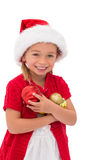 Cute little girl wearing santa hat holding baubles Stock Photography