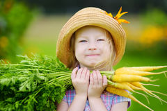 Cute little girl wearing straw hat holding a bunch of fresh organic carrots Royalty Free Stock Photo