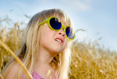 Cute little girl wearing sunglasses, in a warm day Royalty Free Stock Photo