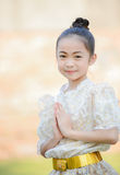 Cute little girl wearing thai dress pay respect. On outdoor background Stock Image