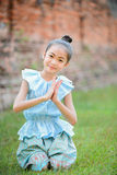 Cute little girl wearing typical thai dress pay respect. On grass Royalty Free Stock Photography