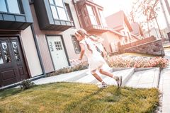 Cute little girl wearing white dress running coming back home stock images