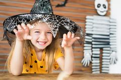 Cute little girl wearing witch hat sitting behind a table in Halloween theme decorated living room, making scary face. Cute little girl wearing witch hat royalty free stock image