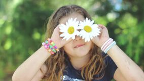 Cute little girl with wet hair, playing with   Shasta daisy flowers, making faces, having fun; positive emotions, slow motion. Cute little girl with wet hair stock video