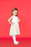 Cute little girl in white dress posing on red background Royalty Free Stock Photos