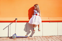 Cute little girl in white dress and scooter Royalty Free Stock Image