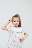 Cute little girl in white dress smiling on camera with long hair Royalty Free Stock Photography