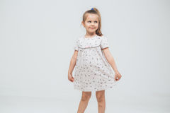 Cute little girl in white dress smiling on camera with long hair Stock Photo
