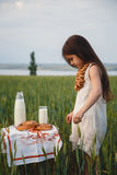 Cute little girl in white dress standing near small table with milk and bread on it in green field. Summertime. Royalty Free Stock Photography