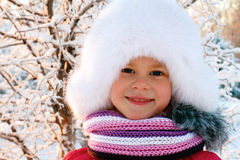 Cute little girl in a white fluffy hat Stock Image