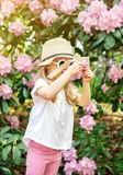 Cute little girl playing with children`s  wooden camera in the park with rhododendron flowers stock photo