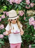 Cute little girl playing with children`s  wooden camera in the park with rhododendron flowers stock images
