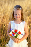 Cute little girl with wild flowers red poppy bouquet Royalty Free Stock Image