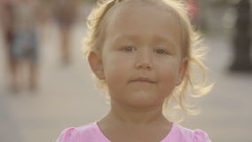 Cute little girl wink to the camera in the public park stock video footage