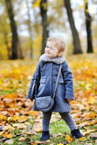 Cute little girl winks - full length outdoors portrait Royalty Free Stock Photo