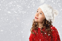 Cute little girl in winter clothes on snow background stock photos