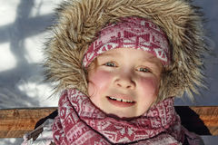 Cute little girl in winter near wood. Cute little girl in winter pink hat and scarf in snow Stock Images