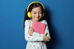 Free Cute Little Girl With Headphones Listening To Audiobook On Background Royalty Free Stock Photo - 176641835