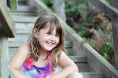 Cute little girl on wooden stairs Stock Photo