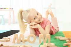 Cute little girl and word MOM composed of wooden letters. On floor at home stock photo