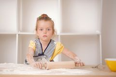Cute little girl working with rolling pin Royalty Free Stock Photography