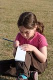 Cute Little Girl Writes Sitting On Grass Stock Photography