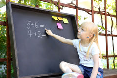 Cute little girl writing answer to the exerciseusing chalk on blackboard Stock Photo