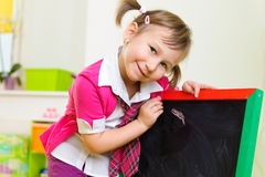Cute little girl writing on chalkboard Royalty Free Stock Image