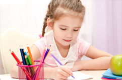 Cute little girl is writing at the desk Stock Image