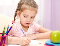 Cute little girl is writing at the desk. At home Stock Photos