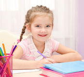Cute little girl is writing at the desk. At home Royalty Free Stock Photos