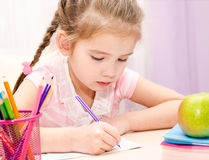 Cute little girl is writing at the desk Stock Photos