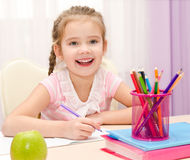Cute little girl is writing at the desk. At home Stock Image
