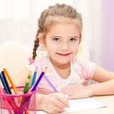 Cute little girl is writing at the desk. At home Stock Images