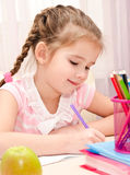 Cute little girl is writing at the desk Royalty Free Stock Photos